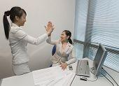 Asian businesswomen high-fiving