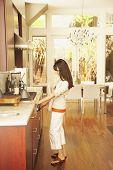 Hispanic woman turning on stove burner