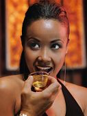 African woman drinking shot at nightclub