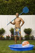Mixed Race man holding net next to kiddie pool