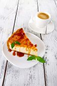 Cheese cake and cup of coffee on wooden background