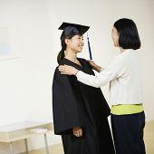 Asian graduate smiling at mother