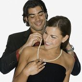 Mixed Race man fastening girlfriend's necklace