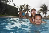 Hispanic father and daughter in swimming pool