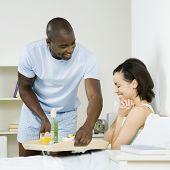 African man serving girlfriend breakfast in bed