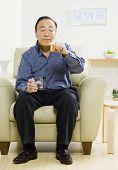 Senior Asian man looking at medication