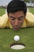 Hispanic man blowing on golf ball