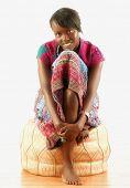 African woman hugging knees