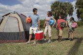 Hispanic family holding sleeping bags next to tent