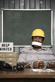 Senior African American male worker chained up behind desk