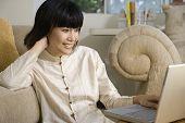 Asian woman looking at laptop