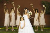 Hispanic bride and bridesmaids holding bouquets