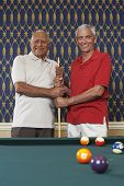 Multi-ethnic senior men holding pool cue