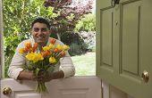 Hispanic man holding bouquet of flowers