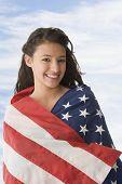 Hispanic teenaged girl wrapped in American flag