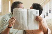 Senior couple hiding behind newspaper
