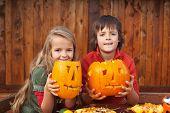 Kids showing their half ready jack-o-lanterns- preparing for Halloween