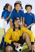 Multi-ethnic children with soccer coach