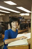 Asian boy using library dictionary