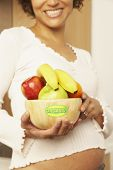 Pregnant Mixed Race woman holding bowl of fruit