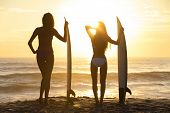 foto of woman bikini  - Rear view silhouettes of beautiful sexy young women surfer girls in bikinis with surfboards on a beach at sunset or sunrise - JPG