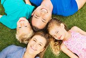 Portrait of Happy Family of Four Outside. Parents and Two Young Children