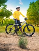 Young Man Wearing Rider Suit With Safety Helmet And Mountain Bicycle Standing In Green Public Park