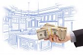 Hand Holding Stacks of Money Over Custom Kitchen Design Drawing.