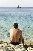 man sitting on rocky beach and watching sailing boat