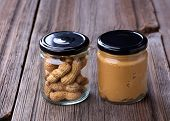 stock photo of jar jelly  - Fresh made creamy Peanut Butter and peanuts in a glass jar on old wooden table - JPG