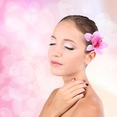 Beautiful young woman with pink flower in hair on bright pink background