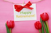 Happy Retirement Card Hanging With Clothespins Over Red Tulips