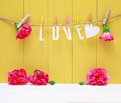 picture of carnations  - Hanging Love letters with pink carnation flowers over yellow wooden wall - JPG
