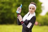Caucasian Sportive Woman Drinking Water During Her Regular Joggong Workout Outdoors.