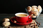 Cup of coffee and tasty cookies on sackcloth napkin, on wooden table, on dark background