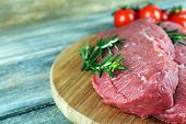 Raw beef steak with rosemary and cherry tomatoes on cutting board on wooden background