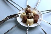Dentist tools with sweets on plate on light background