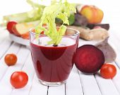 Glass of beet juice with vegetables on wooden table closeup