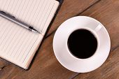 Cup of coffee on saucer with diary and pen on wooden table background