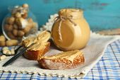 Tasty sandwiches with fresh peanut butter on wooden background