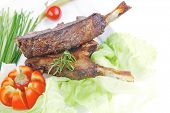 meat plate: roast ribs on white with tomatoes and red hot peppers isolated on white