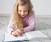 Child reading book at home. Girl doing homework