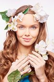 Charming girl in floral wreath holding white flowers