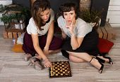 Two Beautiful Girl Friends Playing Chess By The Fireplace