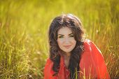 Portrait of a beautiful young woman in summer outdoors in a field.
