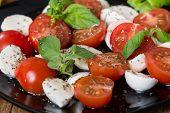 stock photo of black-cherry  - Italian Caprese salad with cherry tomatoes and baby mozzarella on black plate - JPG