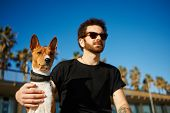 pic of caress  - Strong bearded man in sunglasses sitting in sand with friend dog breed Basenji and looking into the distance enjoying sunlight - JPG