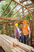 Male construction workers standing in incomplete wooden cabin at site