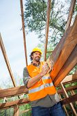 Low angle view of male worker cutting wood with handsaw at construction site