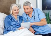 image of male nurses  - Male nurse discussing over digital tablet with senior woman in bedroom at nursing home - JPG